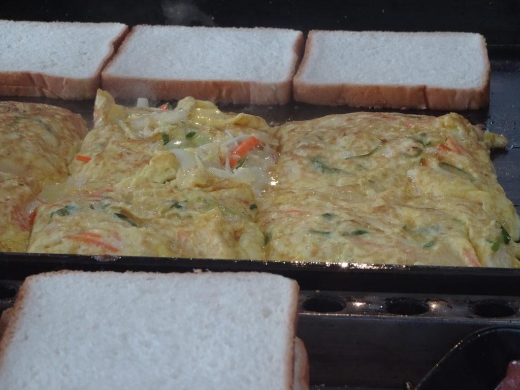 鉄板の上で具になる玉子焼きとトーストのを手際よく焼いていく