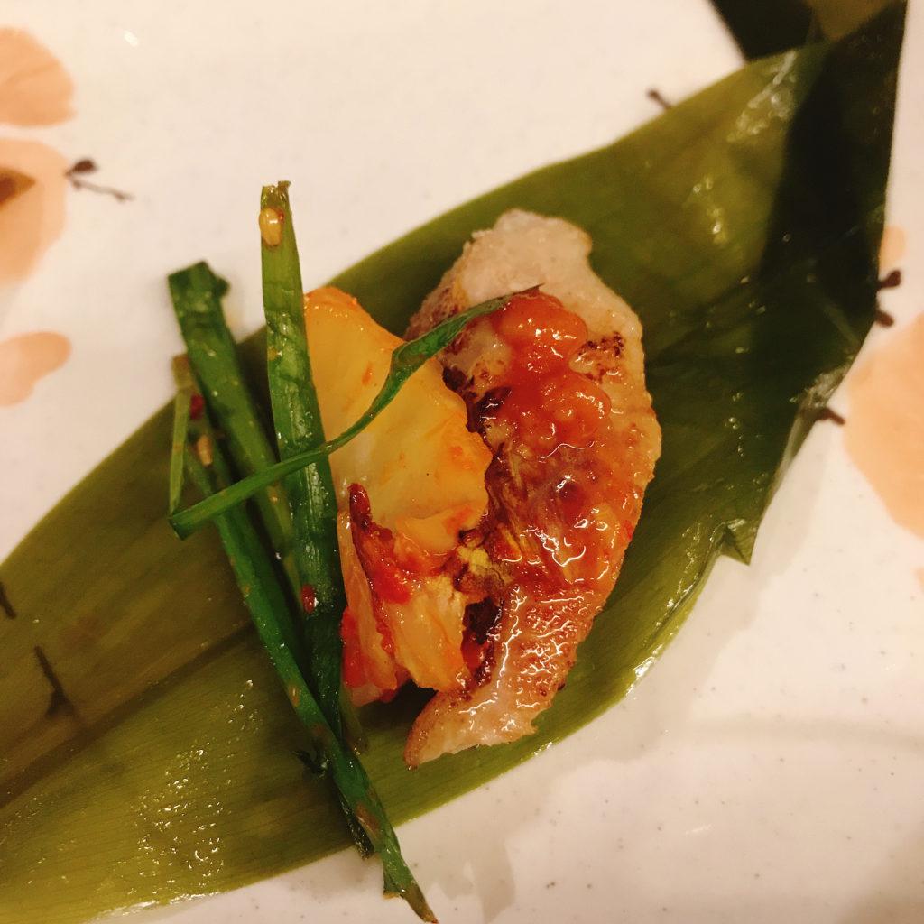 焼いたサムギョプサルと焼いたキムチ、ニラのキムチを行者ニンニクの葉に巻いて食べる